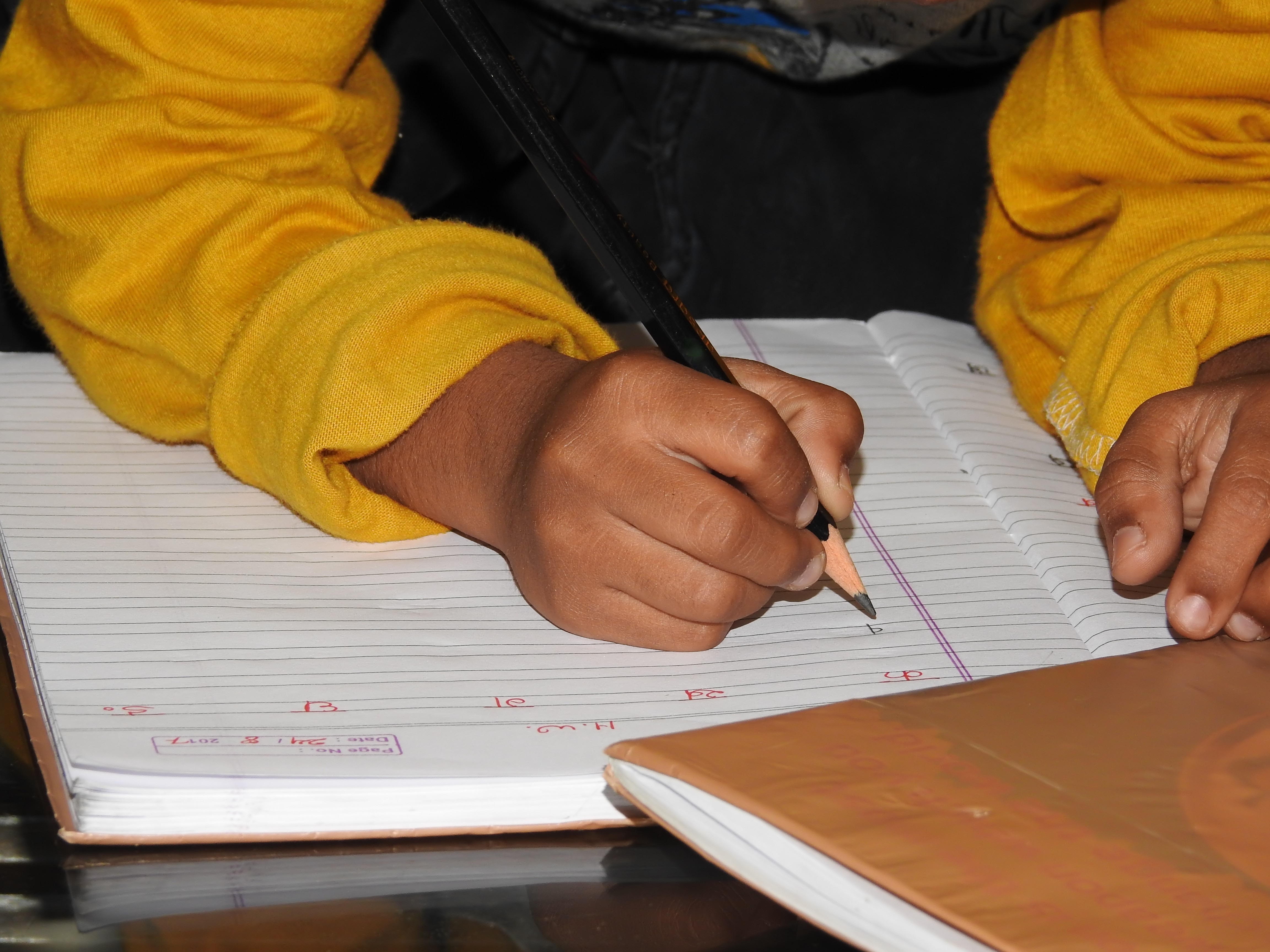 A boy wirtes in a notebook